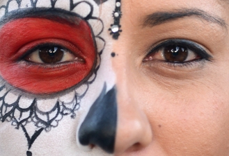 Athena Talmadge poses for a portrait with half of her face painted as a calavera during The Annual Festival of Altars at Garfield Square in the Mission District of San Francisco, Ca. on Wednesday, November 2, 2016, kicking off the celebration of Dia de los Muertos. Families and individuals gathered to honor loved ones who have passed with public altars in the park before a processional of people painted as sugar skulls and dawning colorful clothes made their way throughout the Mission after sunset. Photo by David Andrews.